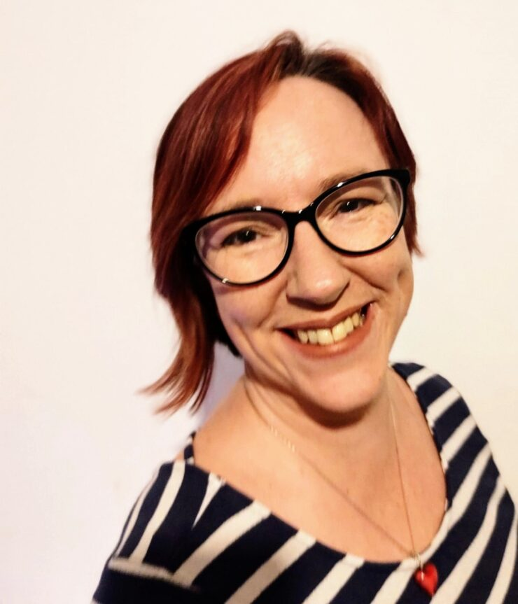 : A lady with short reddy brown hair and brown eyes. She is smiling and wearing black glasses