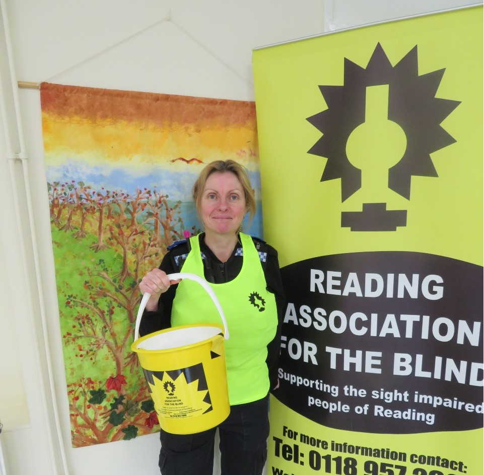 A fundraiser wearing a RAB runnning vest standing next to a banner with the RAB logo on
