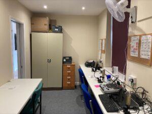 Interior of the RTN studio showing desks, recording equipment, and storage.